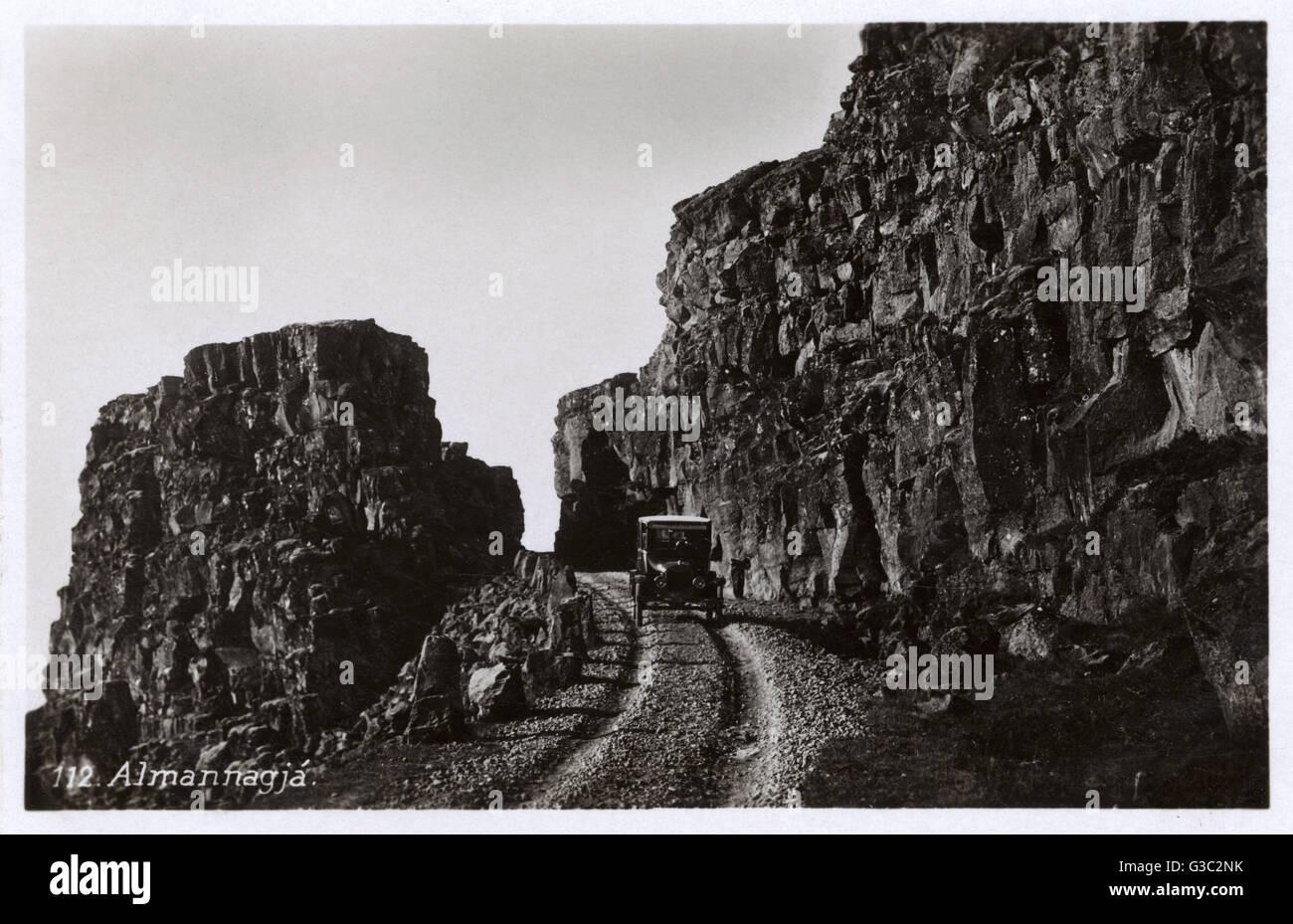 Ein Auto navigiert vorsichtig entlang einer Bahn innerhalb der Almannagja-Schlucht - eine natürliche Bruchlinie Stockbild