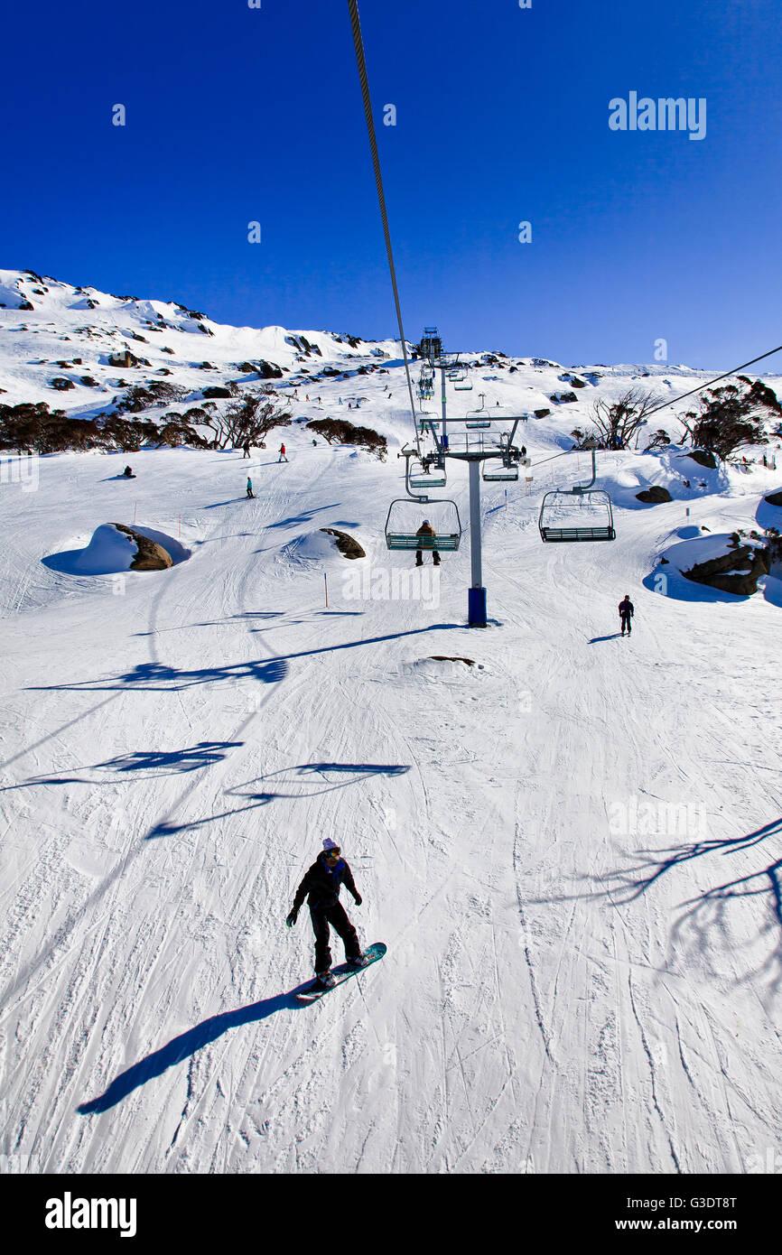 Ski-Sessellift und Kabelinfrastruktur in Perisher Valley der australischen verschneiten Bergen. Beliebtes Skigebiet mit Snowboarder Stockfoto