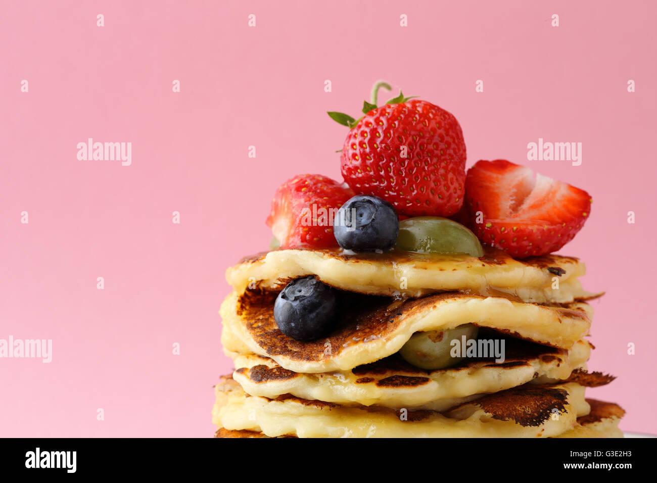 Pfannkuchen mit Beeren vor rosa Hintergrund, Sommer essen Stockbild