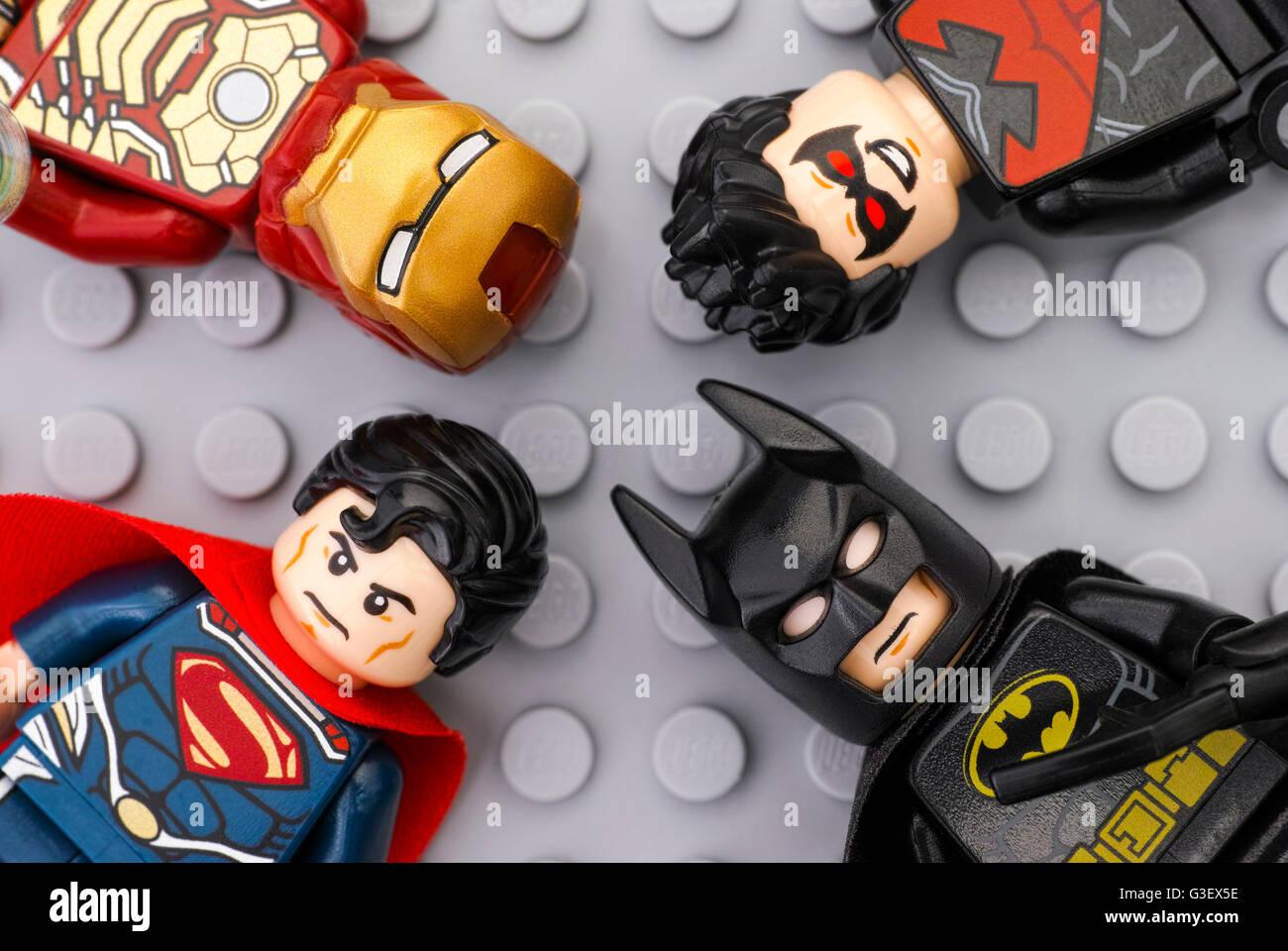 Vier Lego Superhelden - Ironman, Batman, Superman, Nightwing - Minifiguren auf Lego grauer Grundplatte Hintergrund. Stockfoto