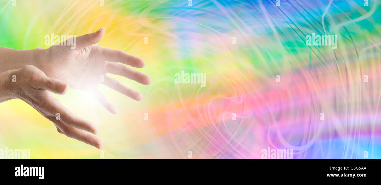 Farbe Heilung Webseite Banner - heilende Hände ausgestreckt mit einem wirbelnden Regenbogen-Energie-Hintergrund Stockbild
