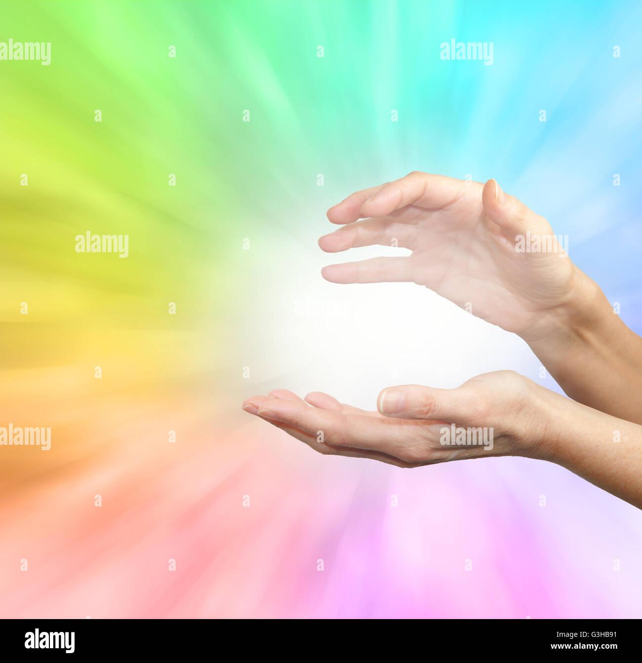 Weibchen ausgestreckt heilende Hände auf weichen nach außen strahlt regenbogenfarbenen Energie-Hintergrund Stockfoto