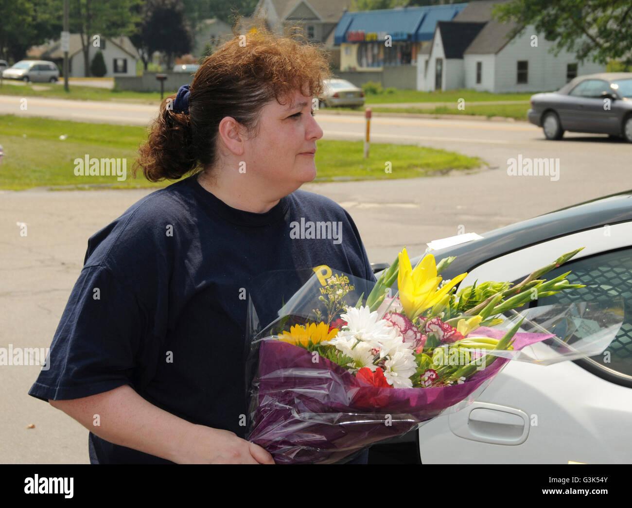 Frau reagiert emotional nach Erhalt der Blumen von einem Verehrer Stockbild