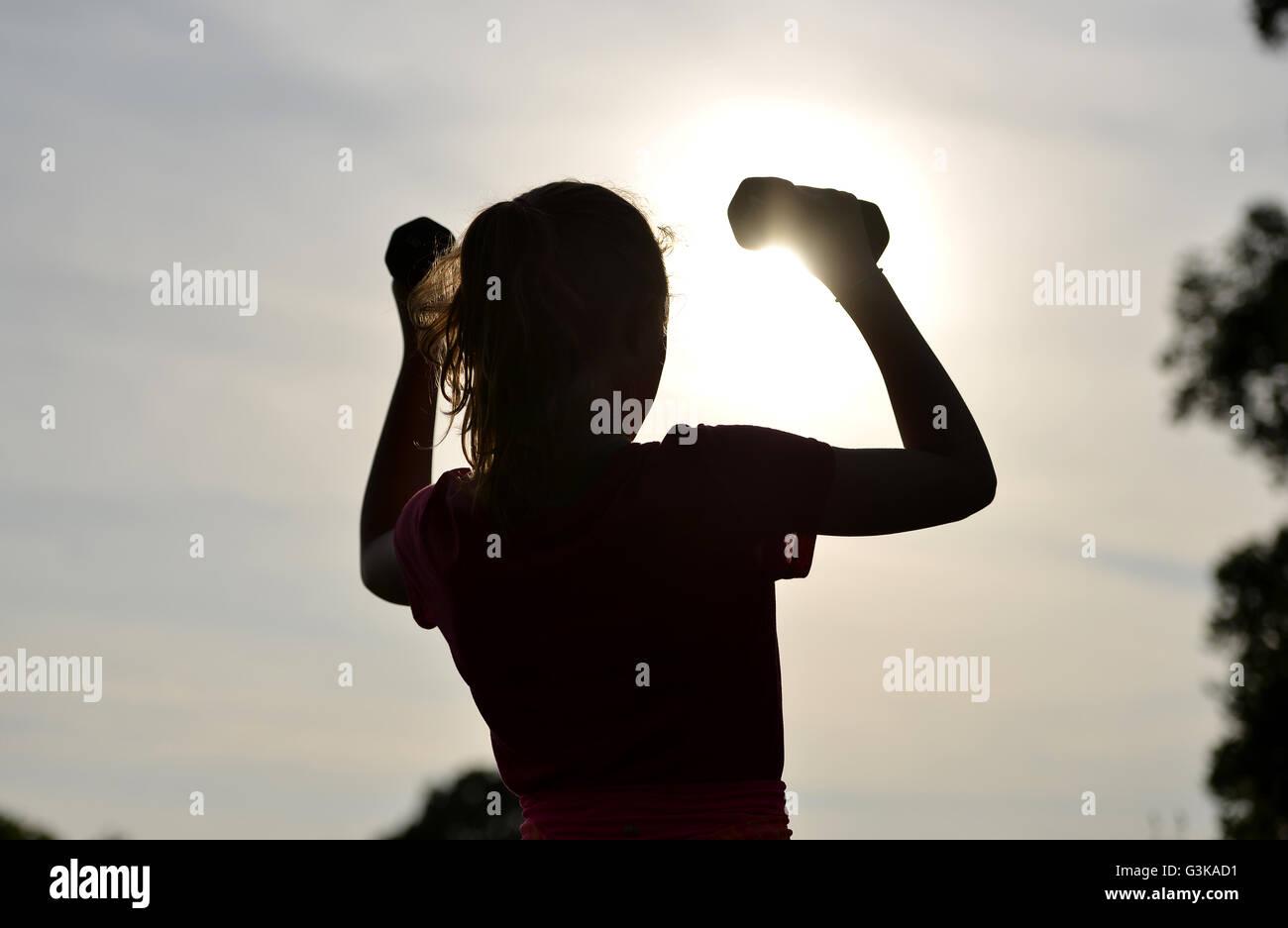 Silhouette eines Mädchens Ausübung außerhalb Stockbild