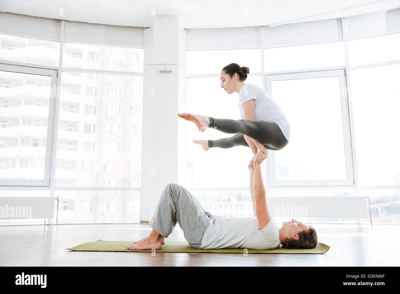 Konzentrierte sich Mann und Frau beim Acro Yoga paarweise im studio Stockfoto