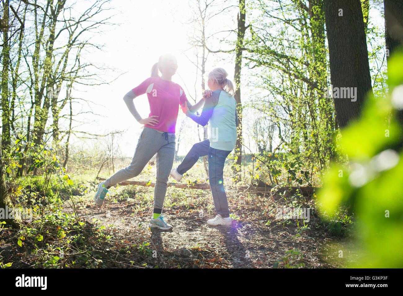 Frauen im Wald von Angesicht zu Angesicht Beine angehoben dehnen Stockbild