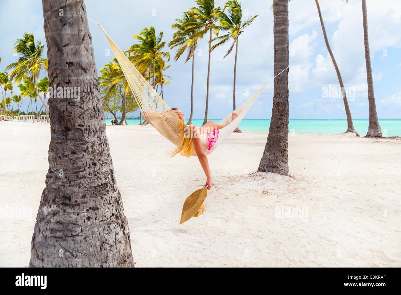 Junge Frau ein Sonnenbad im Palm Tree Hängematte am Strand, Dominikanische Republik, Karibik Stockbild
