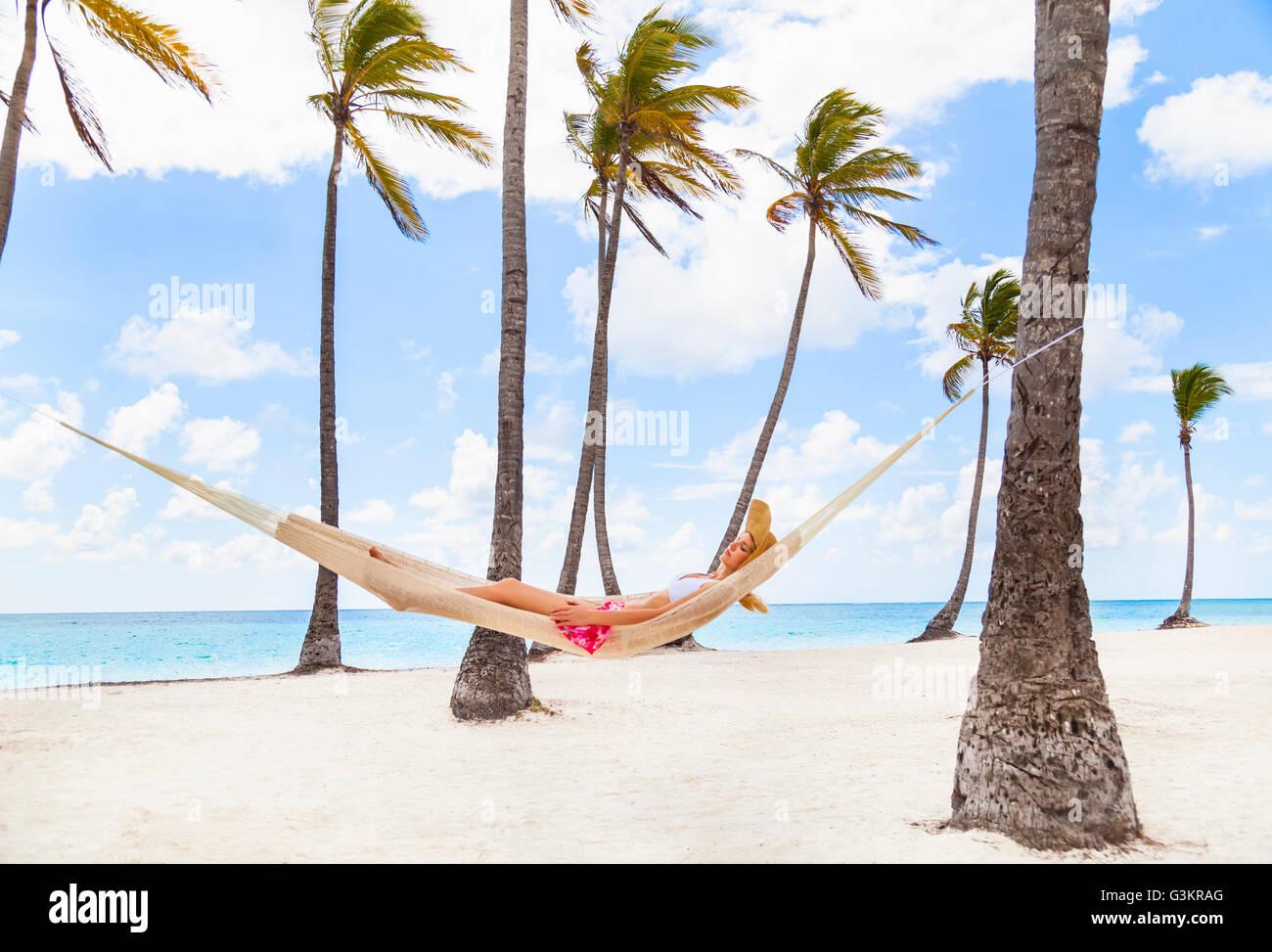 Junge Frau im Palm Tree Hängematte am Strand, Dominikanische Republik, Karibik Stockbild