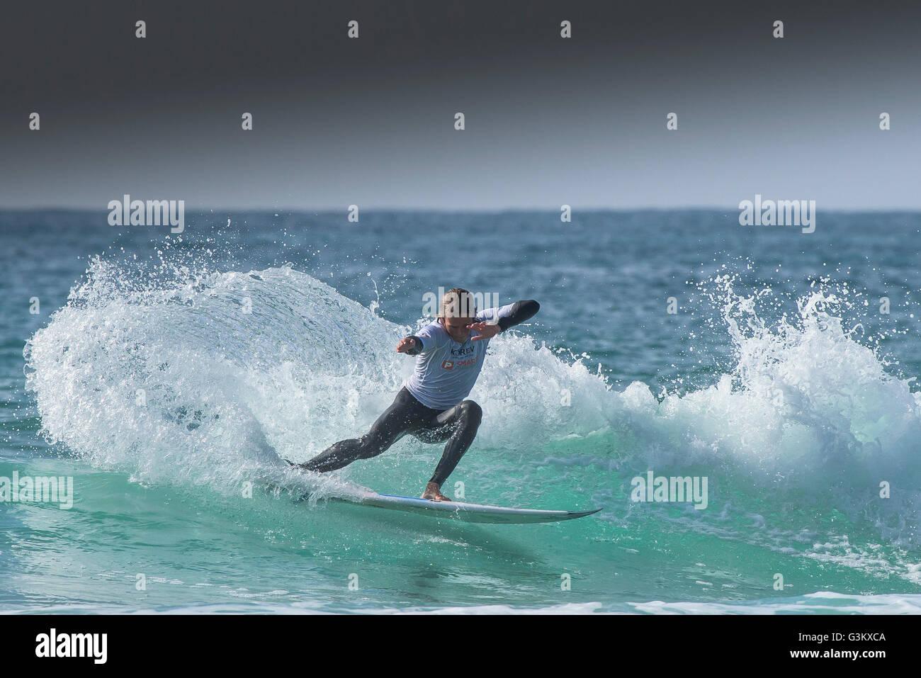 Ein Surfer in spektakulären Aktion wie er in einem UK Pro Surf Tour-Wettbewerb am Fistral in Newquay, Cornwall Stockbild