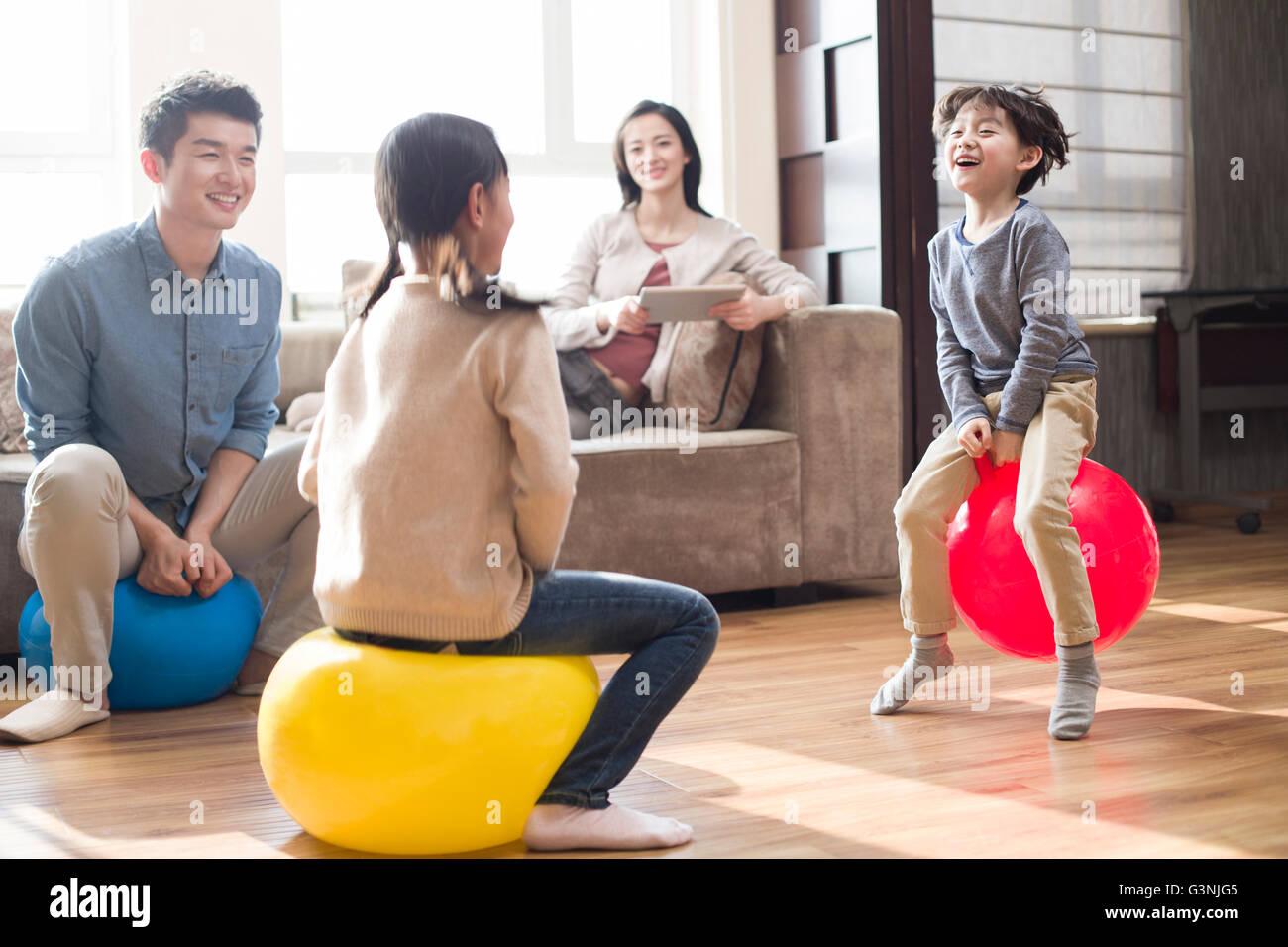 Glückliche junge Familie auf Hoppity Pferde zu Hause sitzen Stockbild