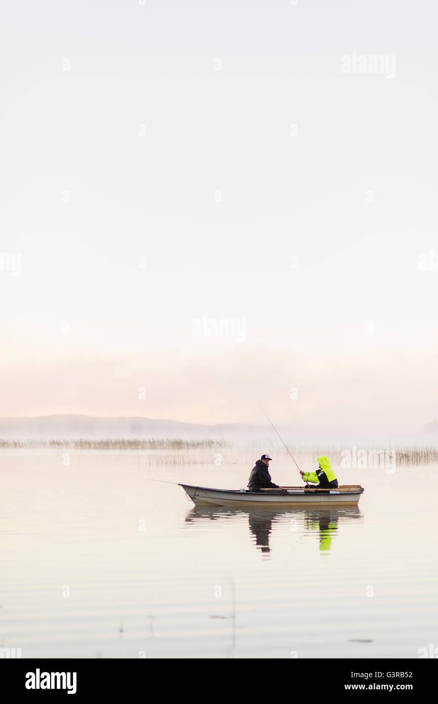 Schweden, Vastmanland, Bergslagen, Torrvarpen, junge Männer Angeln im See bei Sonnenuntergang Stockbild