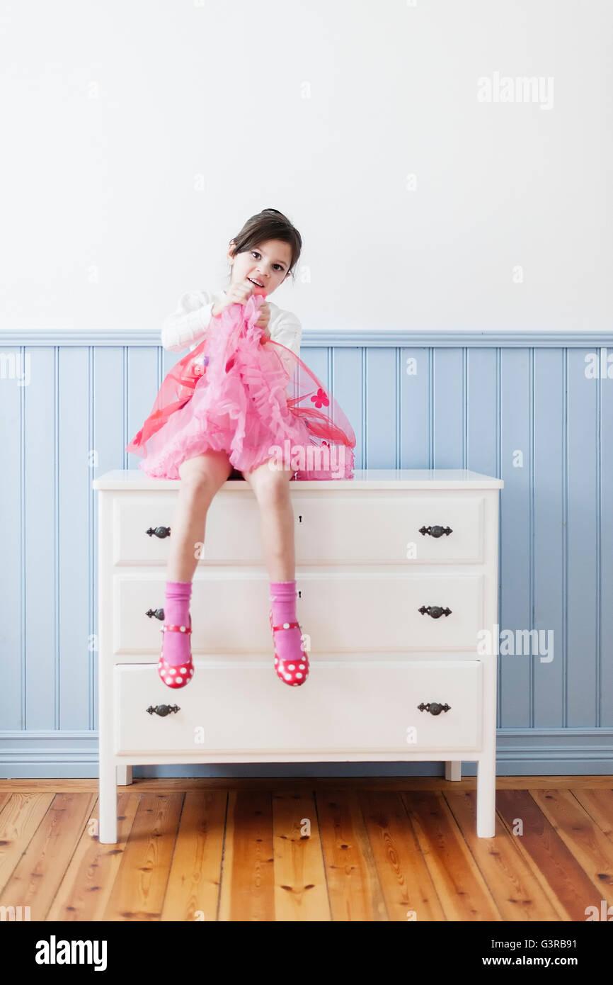 Schweden, kleines Mädchen im rosa Kleid sitzt auf Kommode (4-5) Stockbild