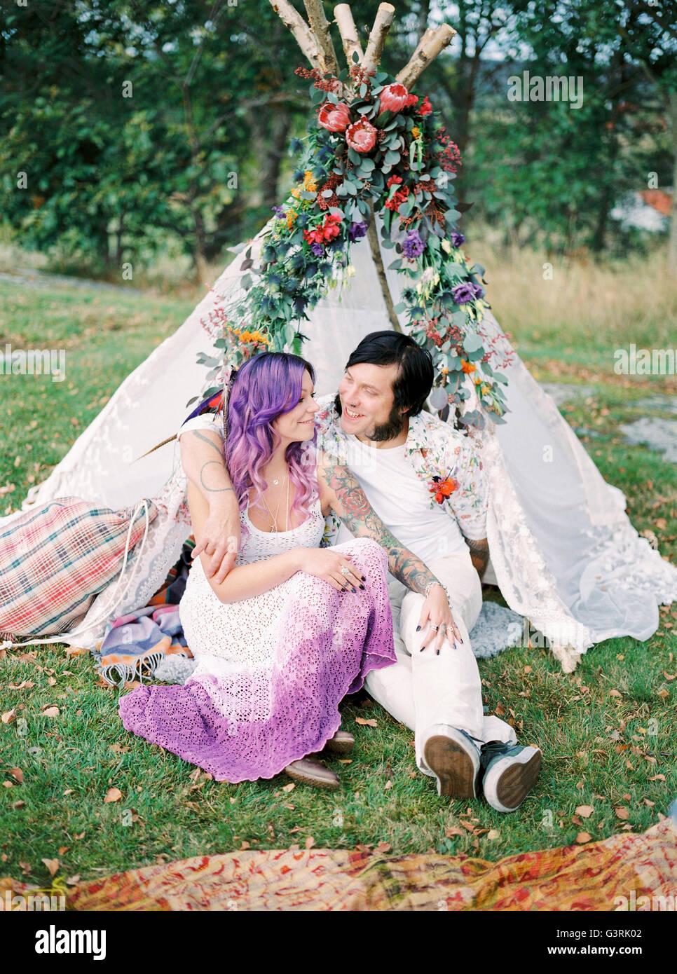 Schweden, Braut und Bräutigam sitzen auf dem Rasen vor weißen Zelt am Hippie Hochzeit Stockbild