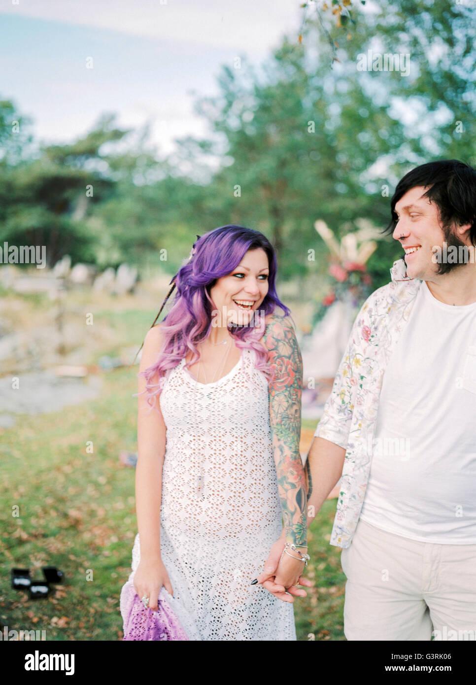 Schweden, Braut und Bräutigam stehen Hand in Hand im Hippie-Hochzeit Stockbild