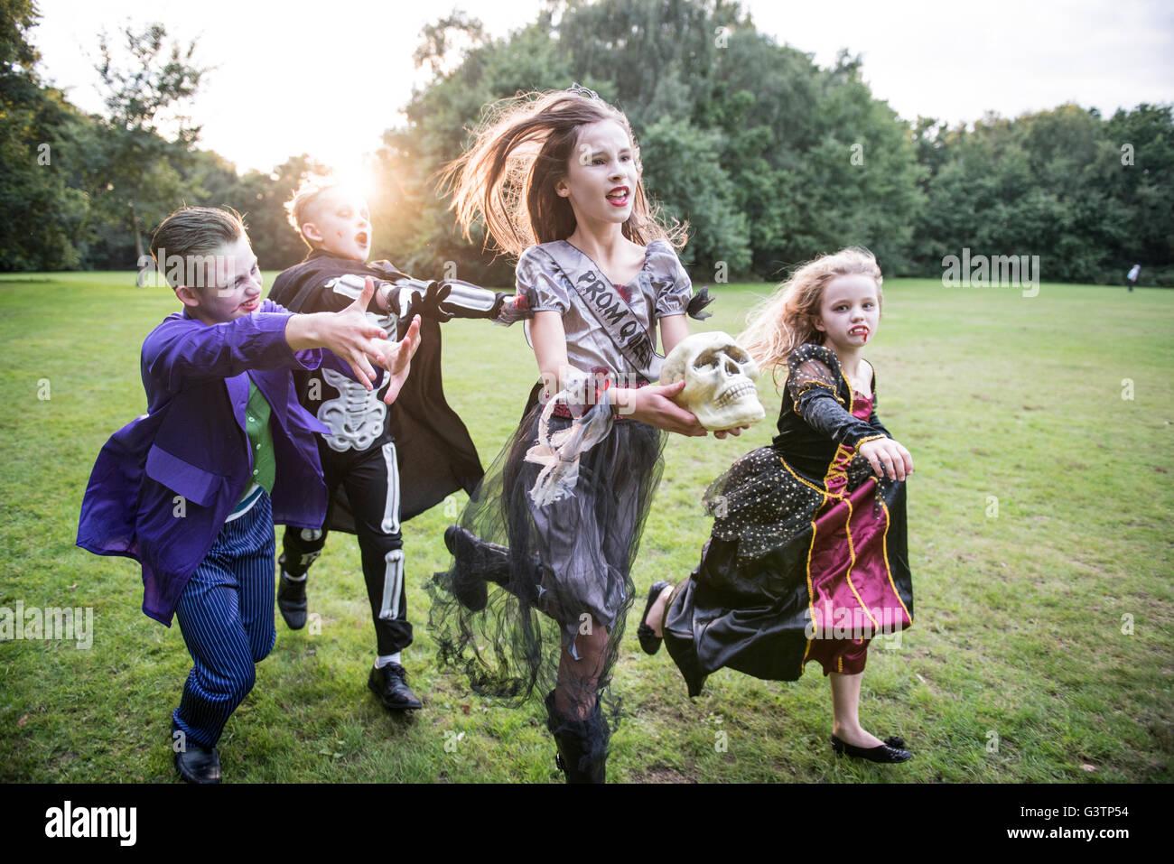 Kinder jagen eine Mädchen gekleidet wie ein Zombie Ballkönigin für Halloween-Nacht. Stockfoto