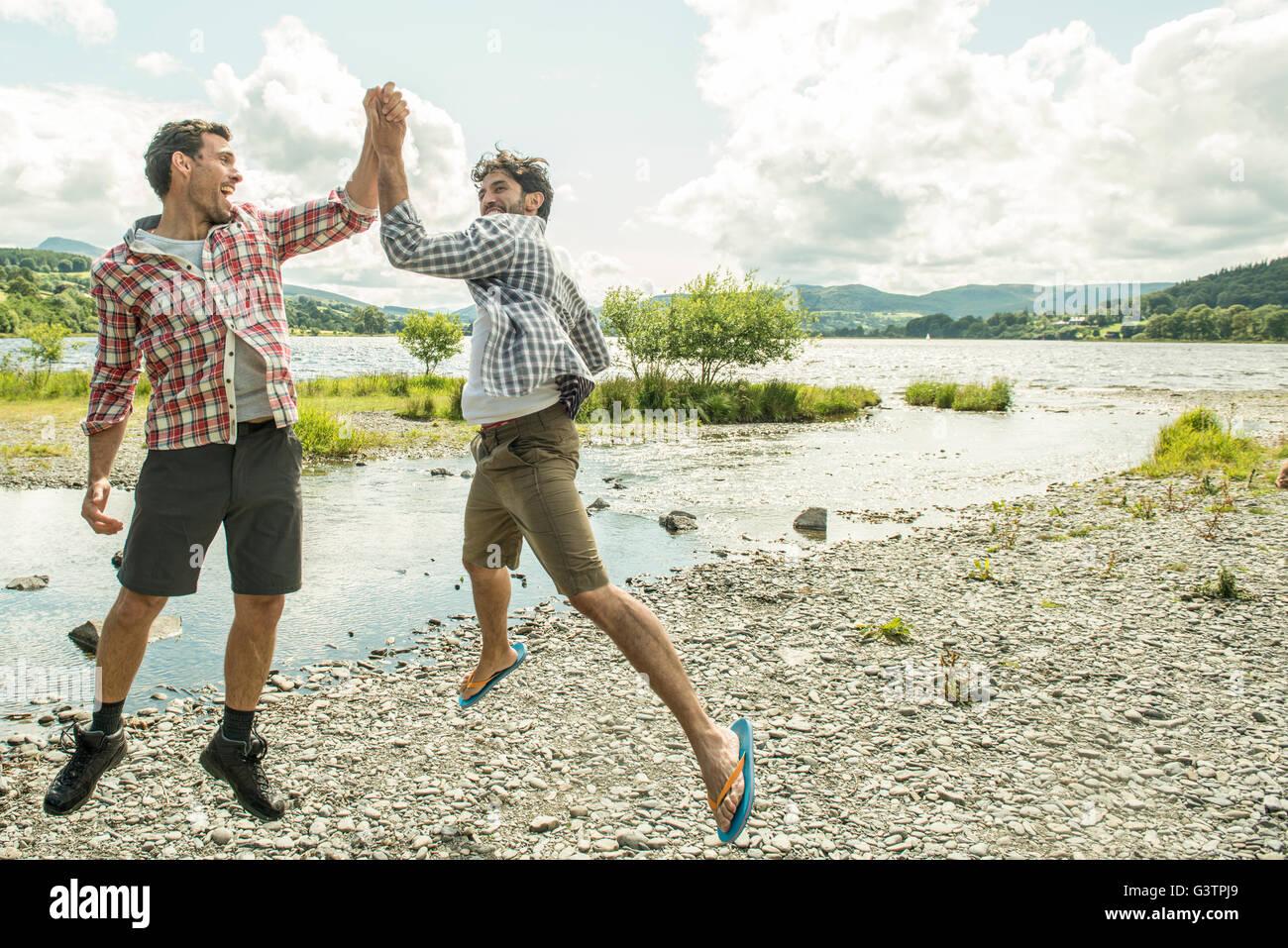Zwei Männer springen hoch fünf in der Nähe von Bala Lake in Wales. Stockbild