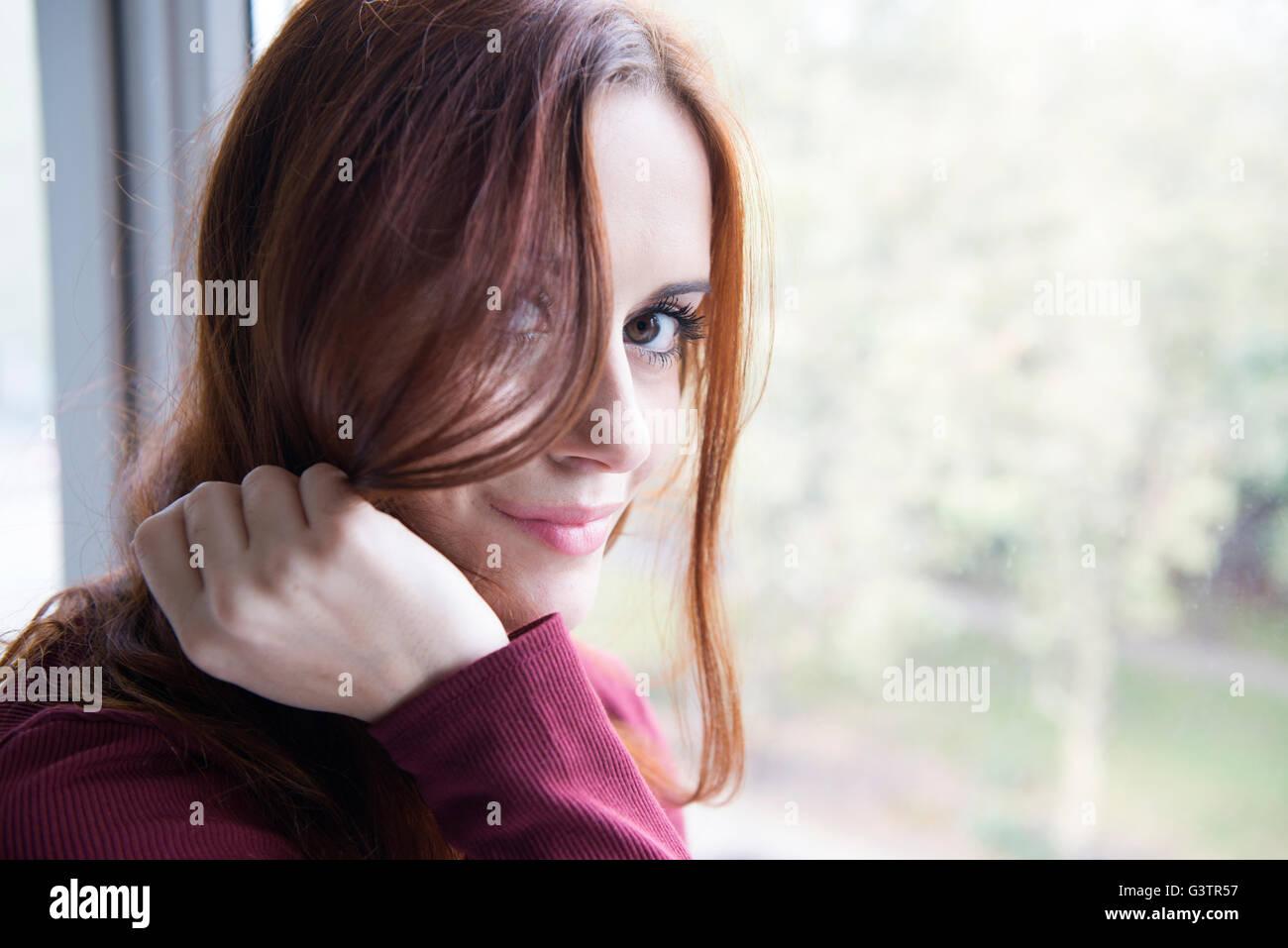 Porträt von einer attraktiven jungen Frau, die ein Fenster sitzen. Stockbild