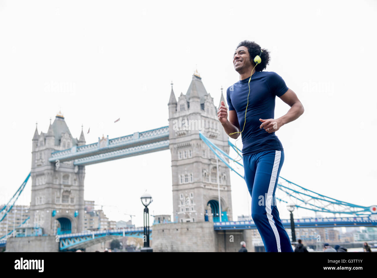 Ein junger Mann Joggen vorbei an Tower Bridge in London. Stockbild