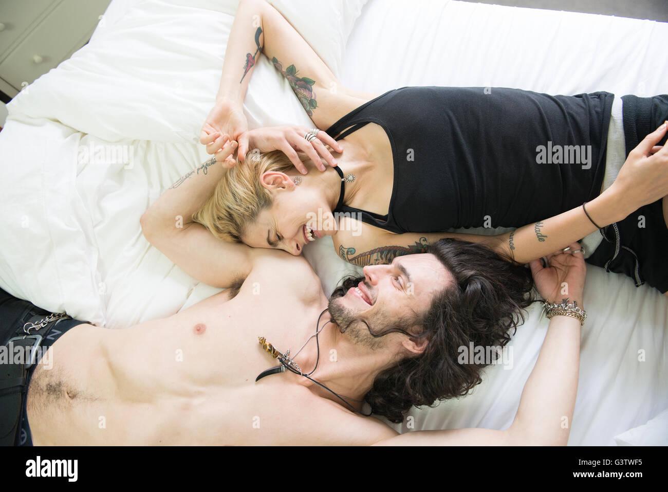 Eine coole junge Tätowierte Paar gemeinsam auf einem Bett liegend. Stockfoto