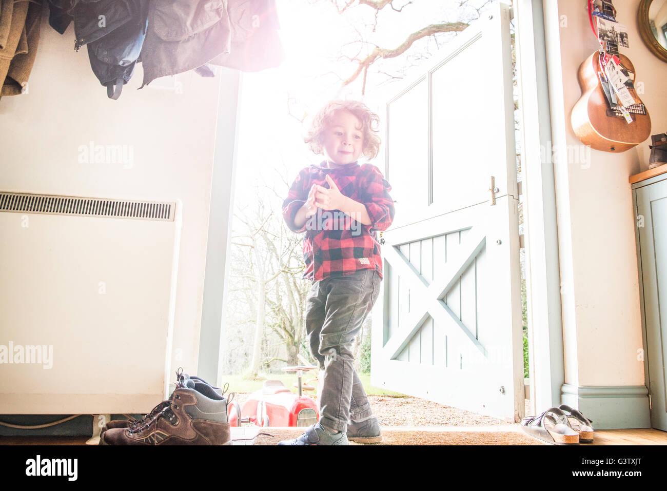 Ein vier Jahre alter Junge stehend an einer offenen Hintertür in einem Check Shirt. Stockbild