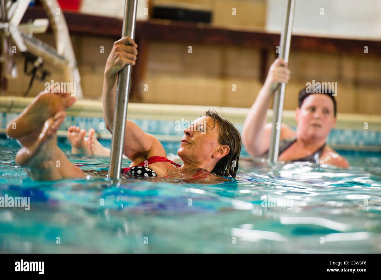 """Hydropole-Schwimmbad-Fitness-Klasse: eine Gruppe von Erwachsenen Reife alte Frauen, die Teilnahme an einem """"Hydropole""""-Pole dance Fitness-Klasse im Wasser in einem Schwimmbad, UK Stockfoto"""