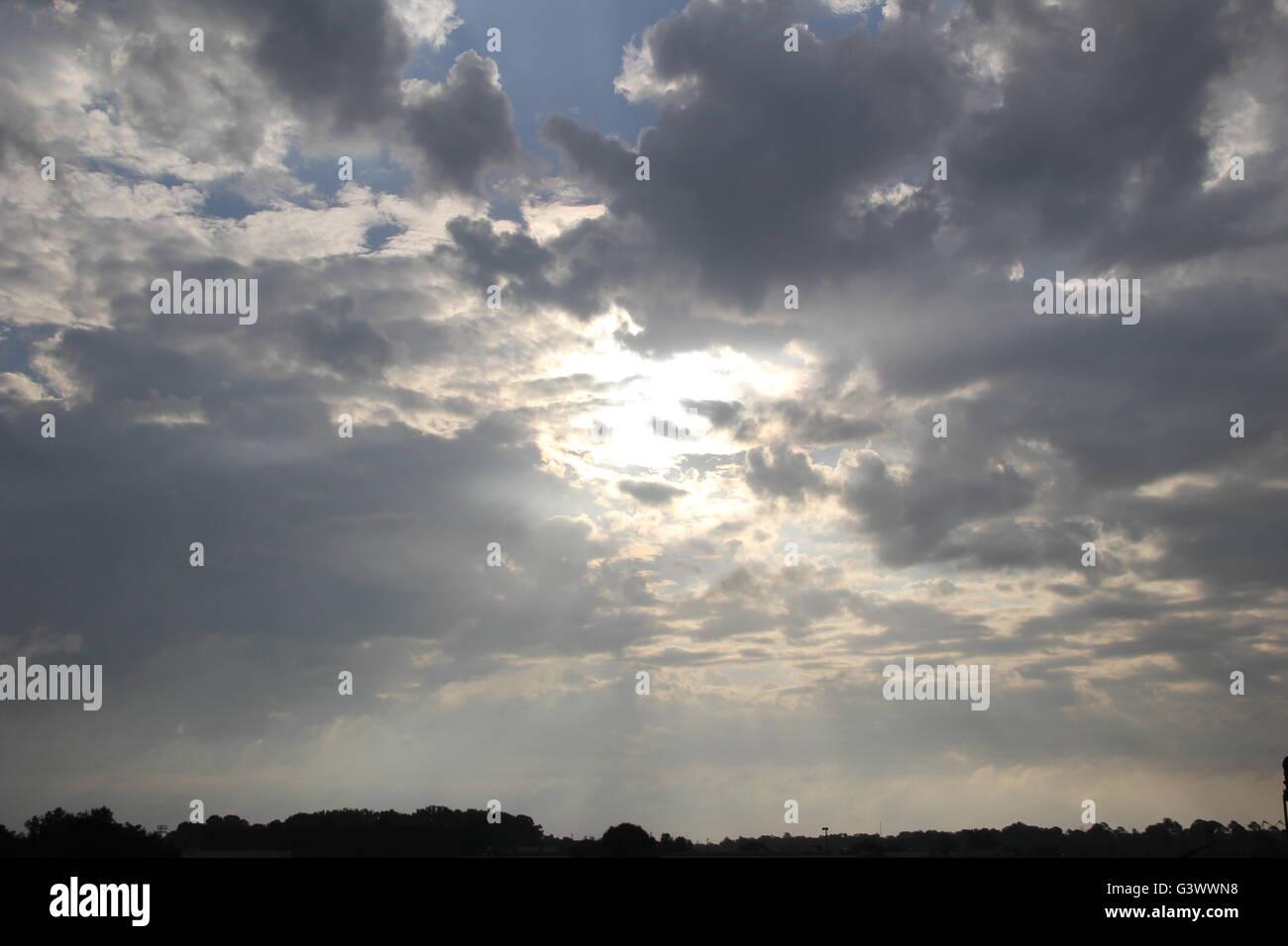 Schöne Strahlen des Sonnenlichts Pierce die durch die dunklen Wolken schaffen leuchtende Strahlen schießen Stockbild