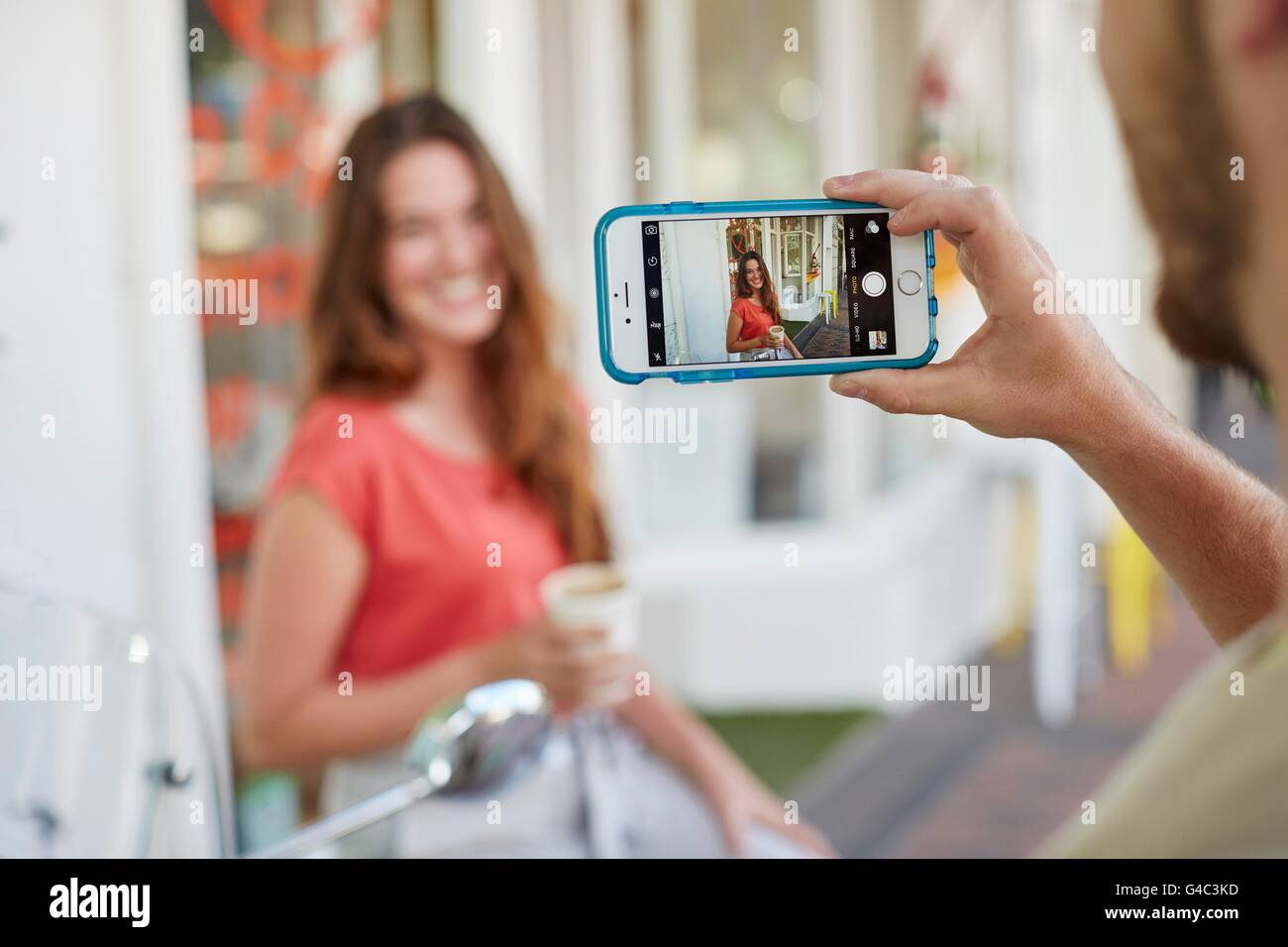 -MODELL VERÖFFENTLICHT. Foto der Person nehmen jungen Frau mit Smartphone. Stockbild
