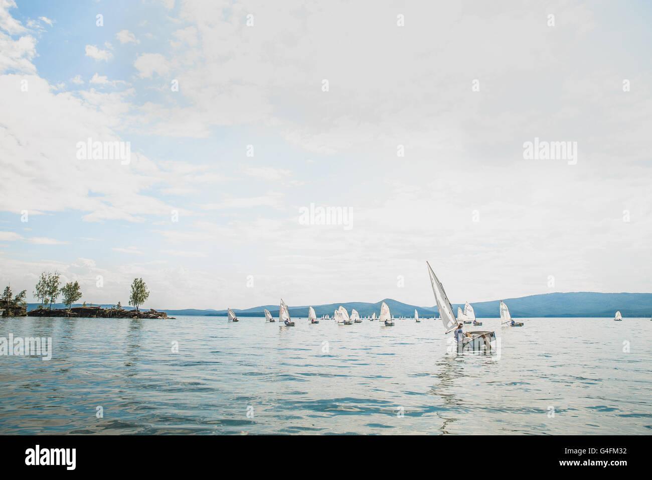 Gruppe junger Sportler auf Boote der Optimist-Klasse Segeln auf See Cup Regatta Fyodor Konyuhov Stockbild