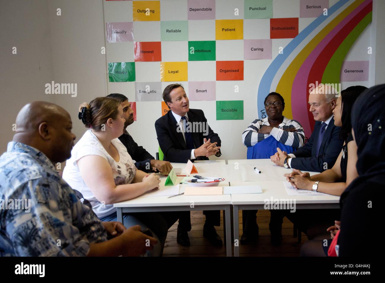 Premierminister David Cameron und der Staatssekretär für Arbeit und Pensionen Iain Duncan Smith nehmen an einer übertragbaren Schulung Teil, während sie die A4E (Action for Employment) Büros in Brixton im Süden Londons besuchen. Stockfoto