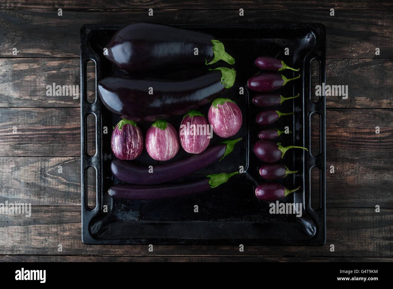 Auberginen Sorten auf rustikalen Backblech angeordnet. Draufsicht mit Textfreiraum Stockbild