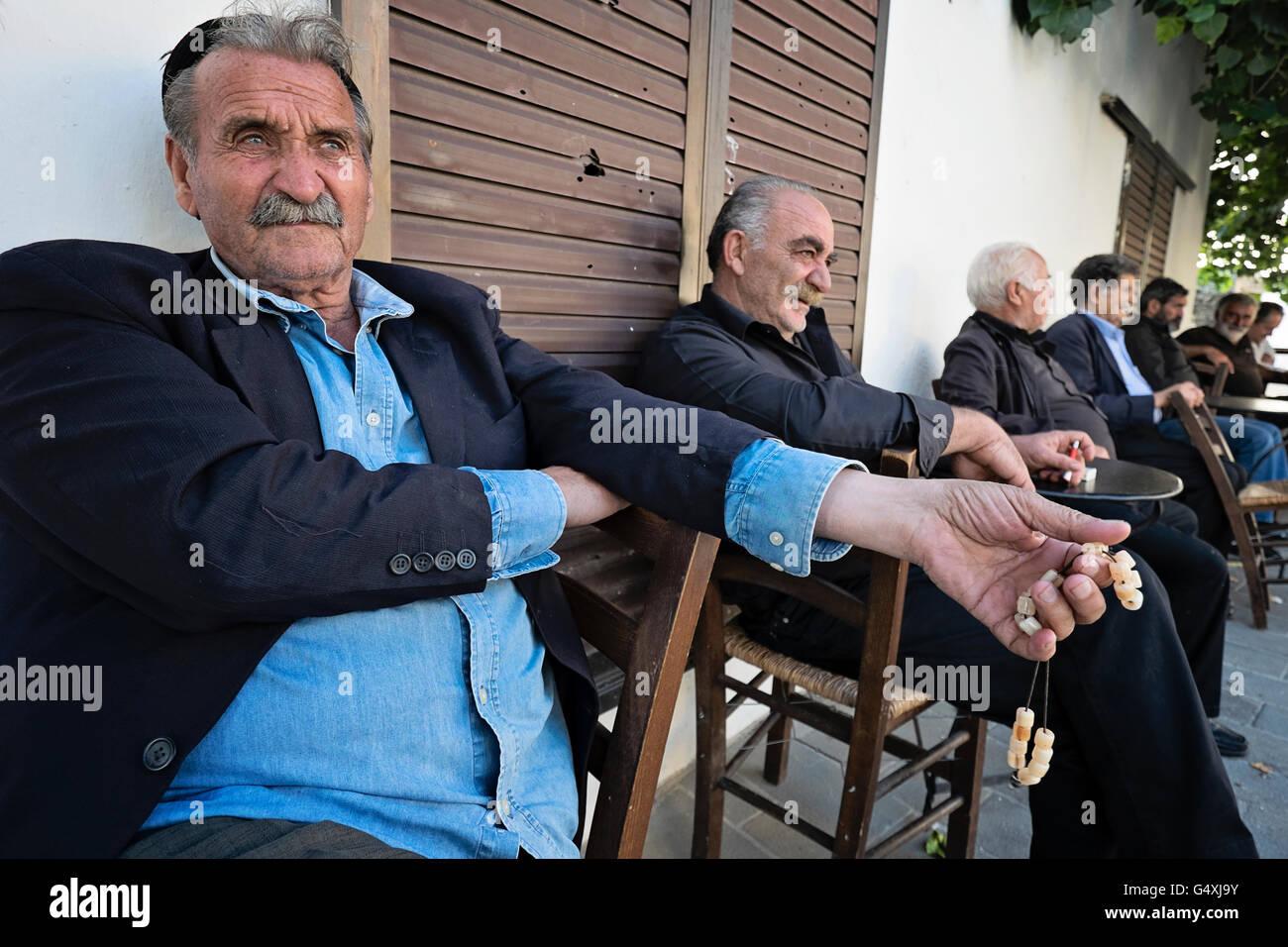 Männer mittleren Alters entspannen Sie auf dem Bürgersteig in Anogia auf Kreta in Griechenland Stockfoto