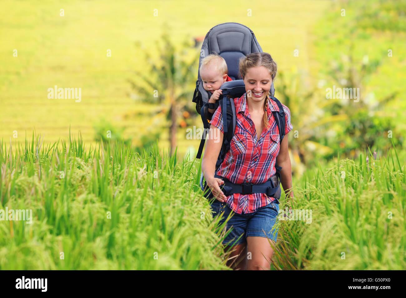 Naturspaziergang in grünen Terrasse Reisfeld. Glückliche Mutter halten wenig Reisende im Rucksack. Baby Stockbild