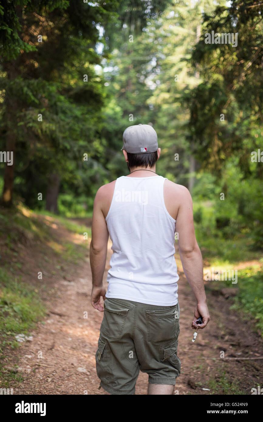 Junger Mann zu Fuß durch den Wald Stockfoto