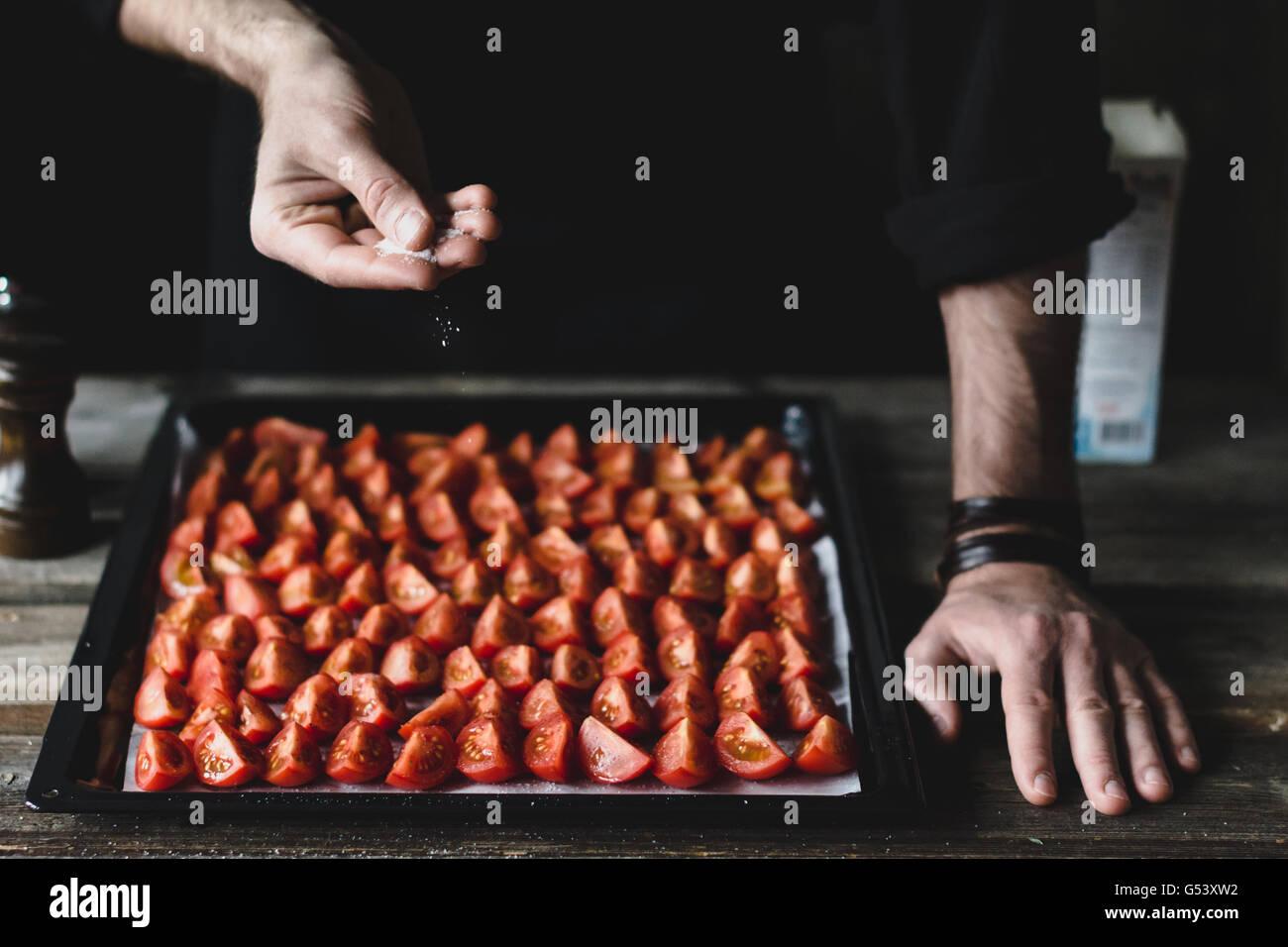 Männliche Küchenchef Salzen Sie Tomaten auf einem Tablett. Cherry-Tomaten vorbereiten zum Braten Stockbild