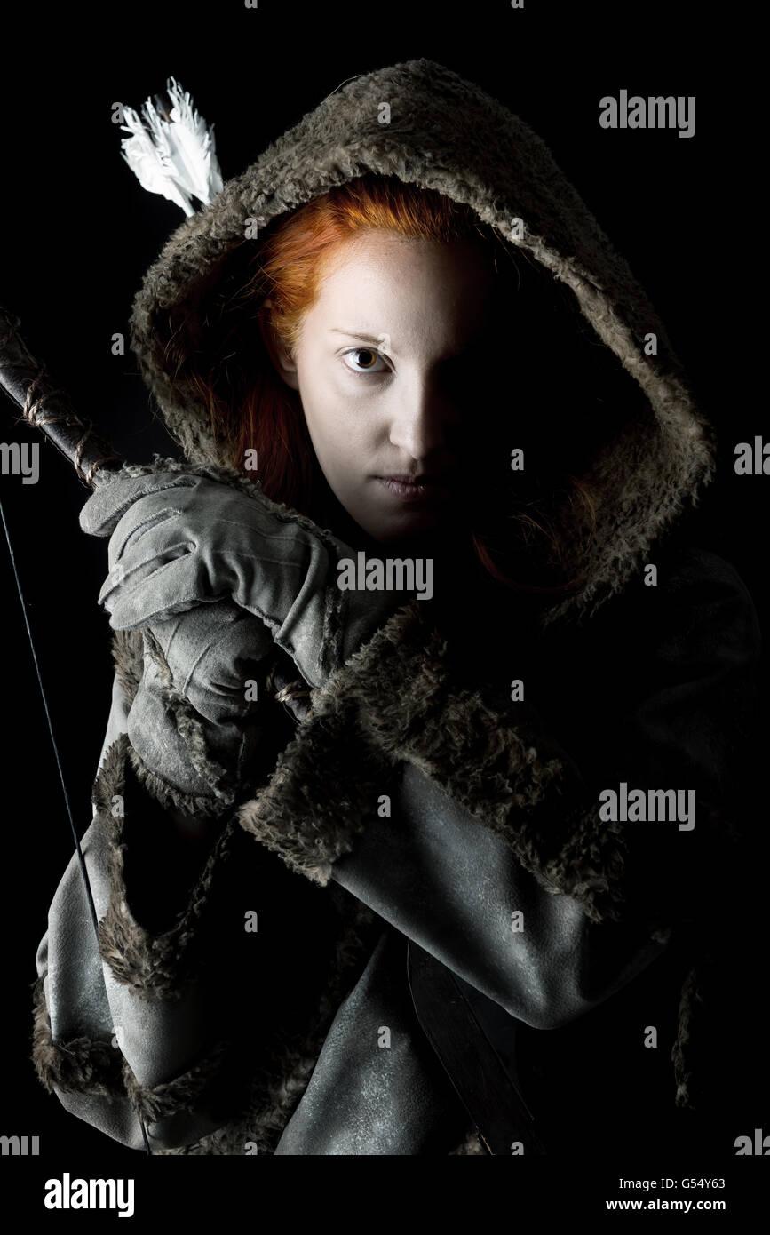 Mädchen Bogenschütze in einem Kostüm mit Bogen in einem dunklen Hintergrund isoliert Stockfoto