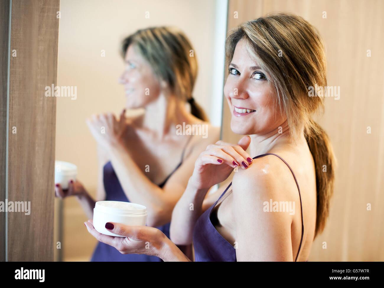 Fröhliche schöne Frau Anwendung Kosmetik Stockbild