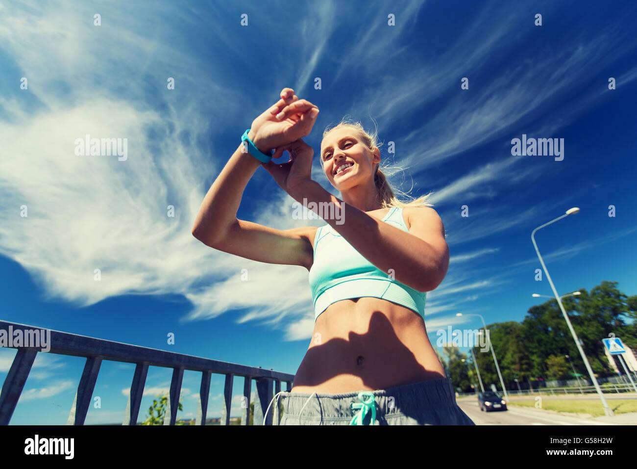 glückliche Frau mit Herzfrequenz-Uhr und Kopfhörer Stockbild