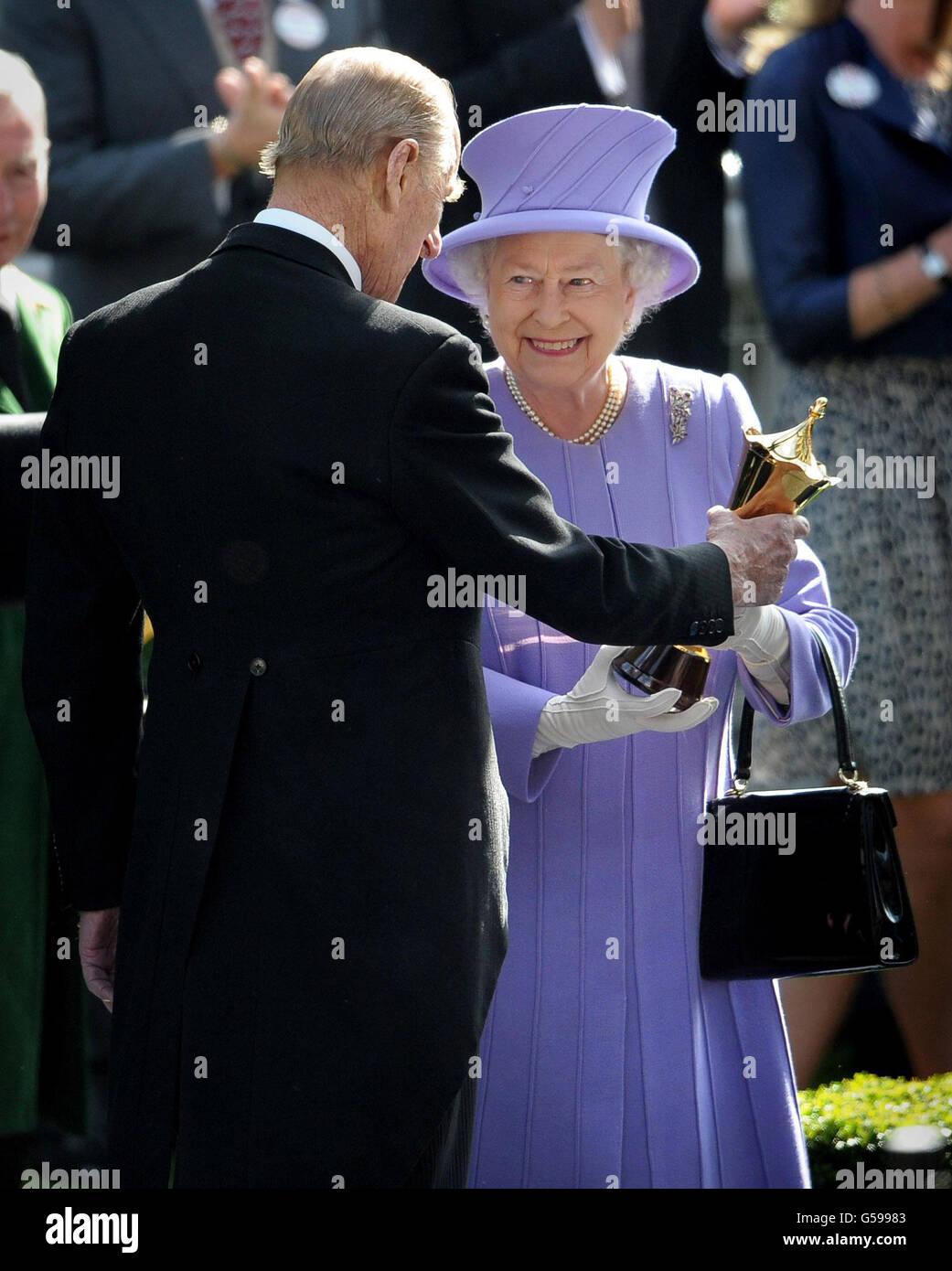 Königin Elizabeth II. Erhält die Trophäe vom Herzog von Edinburgh, nachdem ihr Pferd Estimate am vierten Tag des Royal Ascot Meetings 2012 auf der Ascot Racecourse, Berkshire, die Vase der Königin gewonnen hat. Stockfoto