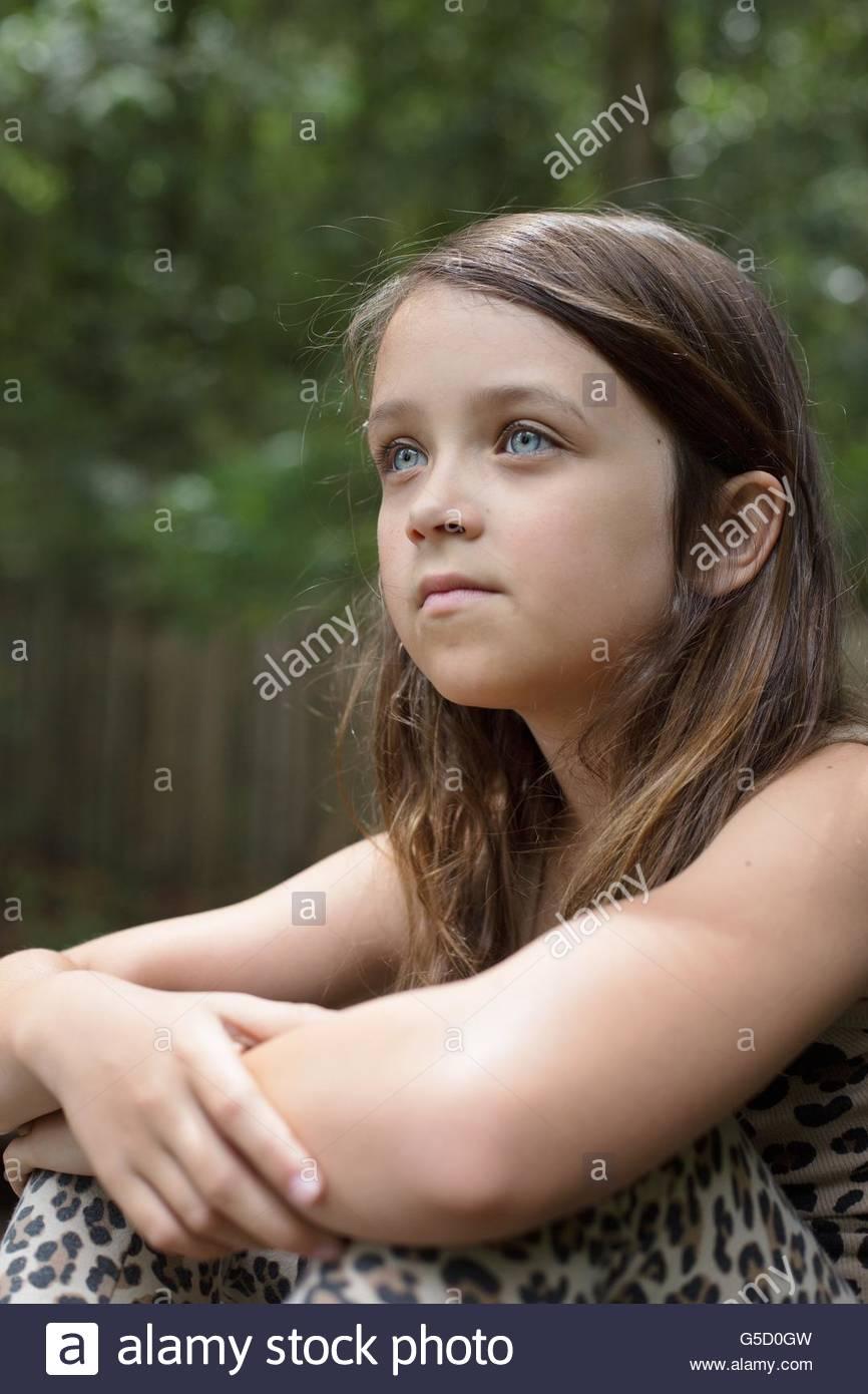 Ein acht Jahre altes Mädchen, sitzend mit Arme um die Knie Stockfoto ...