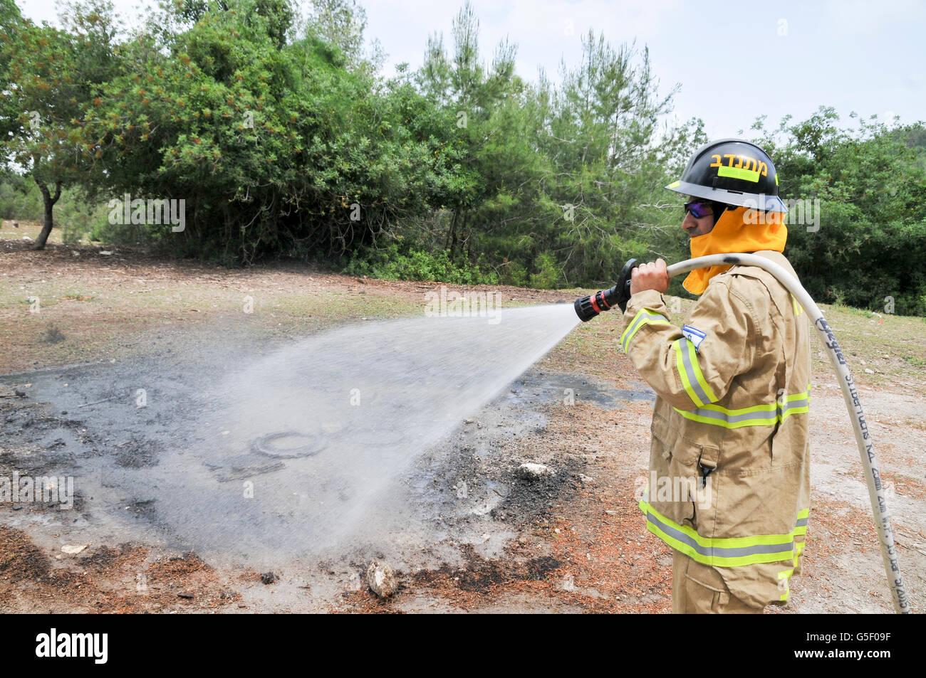 Feuerwehrmann in Schutzkleidung löscht ein Feuer als Bestandteil eine Brandbekämpfung Bohrer Stockbild