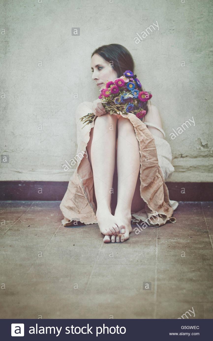 Junge Frau sitzt auf der Terrasse mit Blumen Stockbild