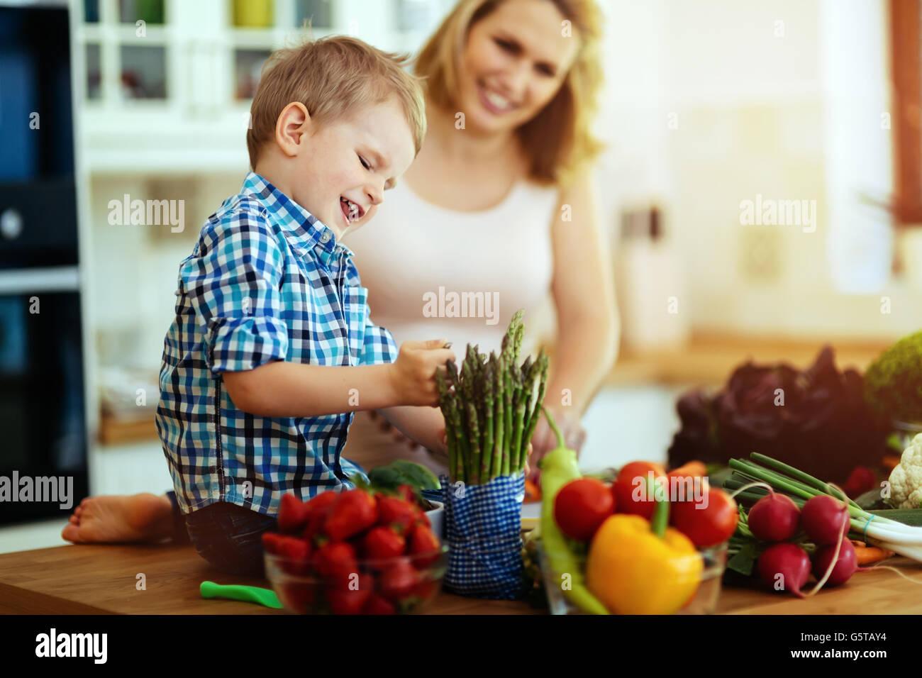Mutter und Kind bereitet Mittagessen in Küche Stockbild