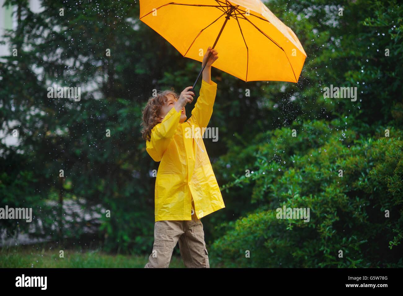 Kerlchen mit einem leuchtend gelben Schirm und in einem Regenmantel unter warmen Sommerregen. Er liebt den Regen Stockbild
