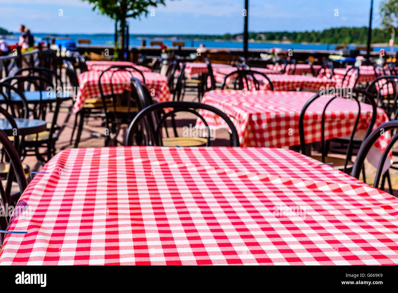 Rot-weiß karierten Tischdecken in einer Outdoor-lokal mit Küste im Hintergrund. Kopieren Sie Speicherplatz Stockbild