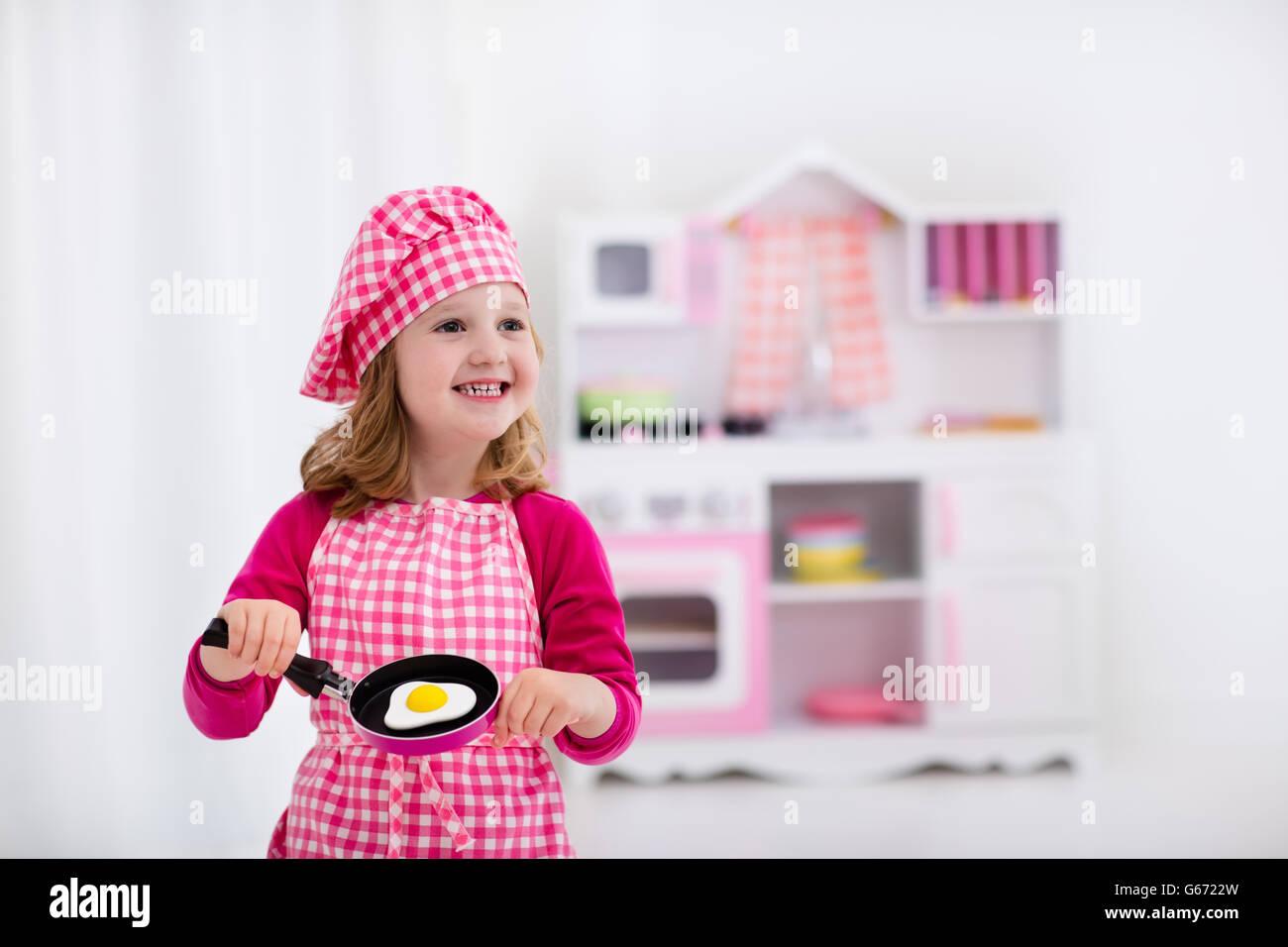 Kleine Mädchen und jungen in Koch Hut und Schürze Spiegeleier in ...