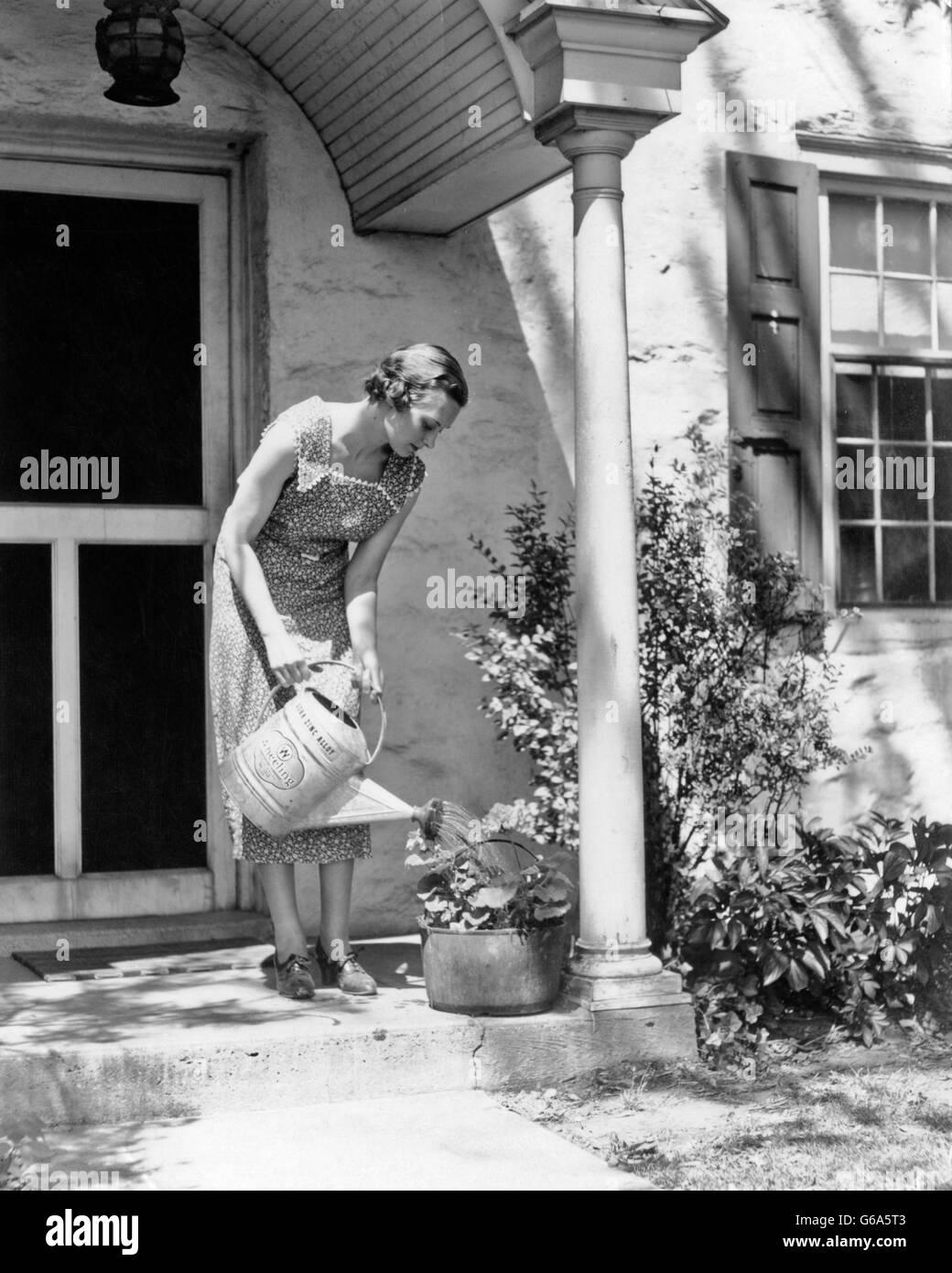 1930ER JAHREN FRAU PRINT KLEID BEWÄSSERUNG TOPFPFLANZE MIT GIEßKANNE AUF VORDEREN STOOP DES HAUSES Stockbild