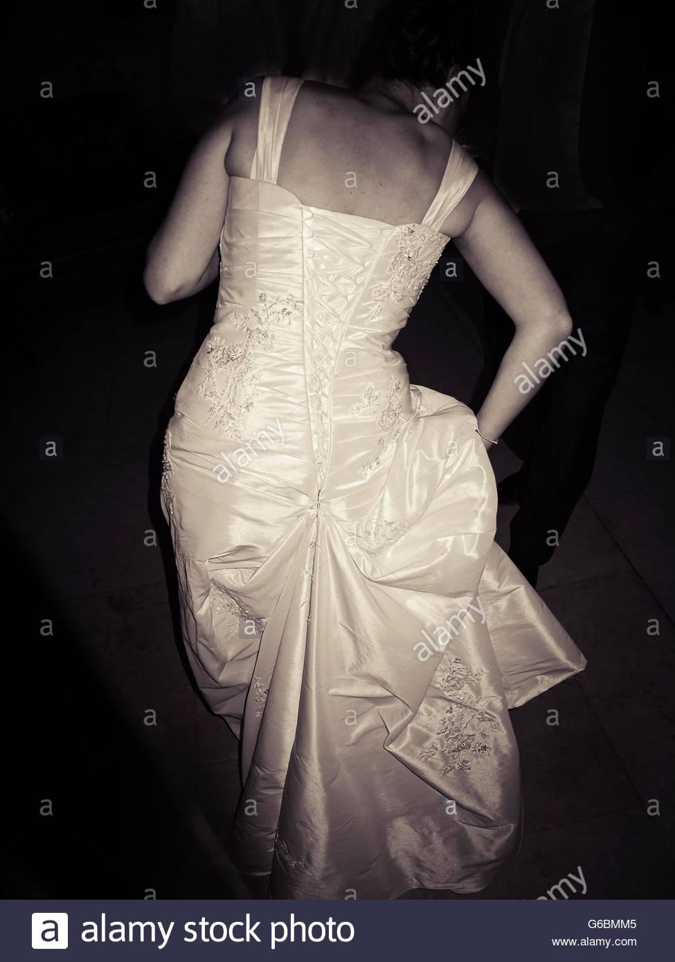 Rückansicht der Braut im Hochzeitskleid in der Nacht Stockbild