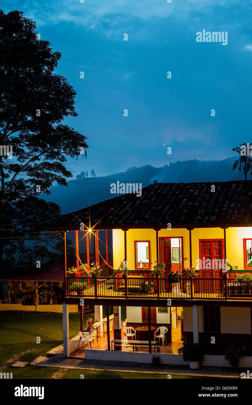 Ein Haus leuchtet warm in der Abenddämmerung auf einer Kaffeefarm in ländlichen Kolumbien. Stockbild