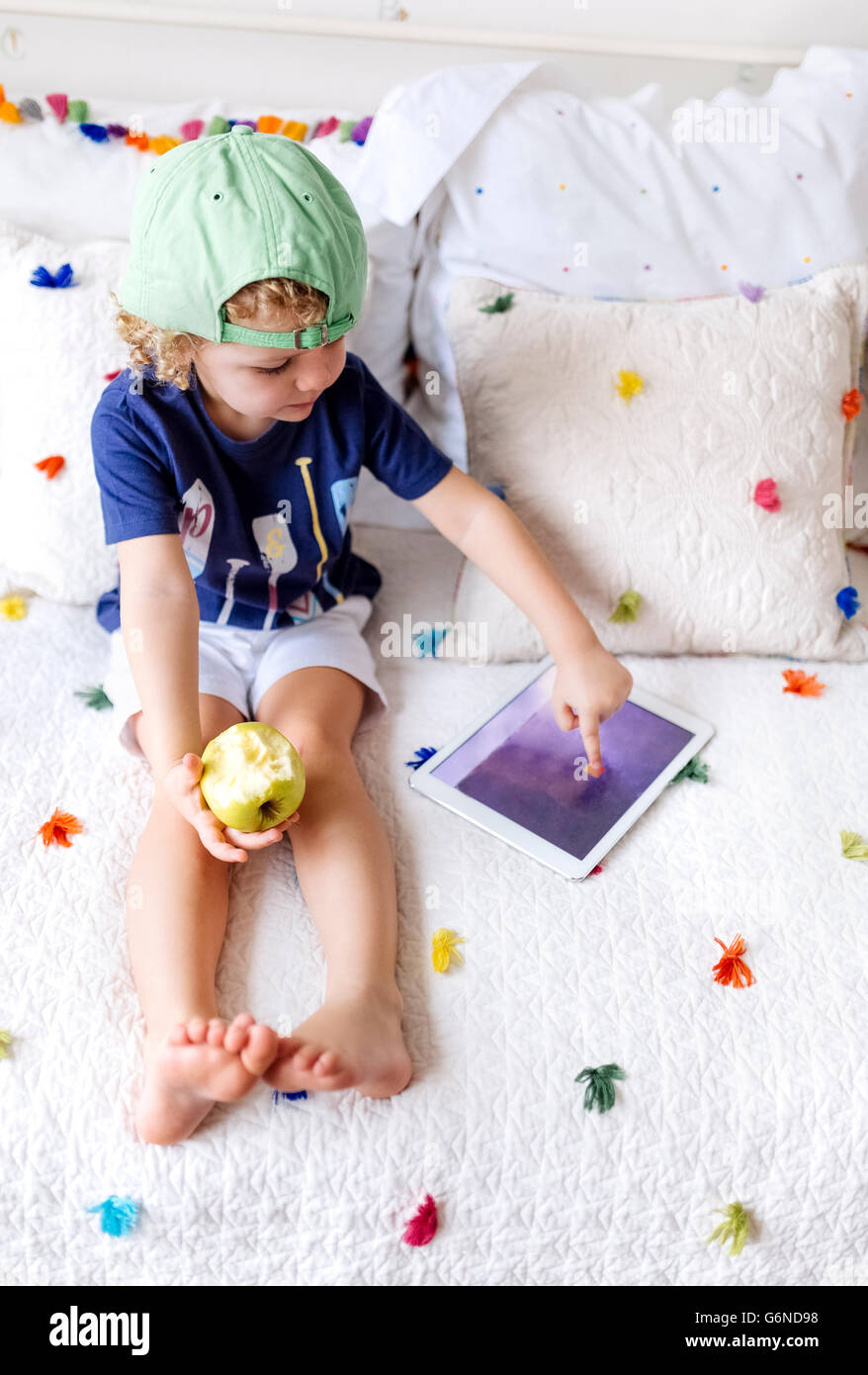 Kleiner Junge sitzt auf der Couch mit einem Apfel mit digital-Tablette Stockbild