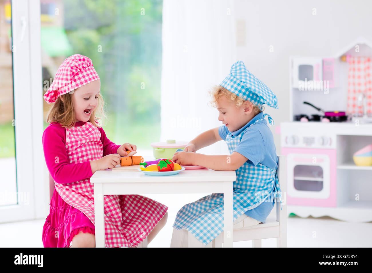 Kleine Mädchen und jungen in Koch Hut und Schürze in Spielzeug Küche ...